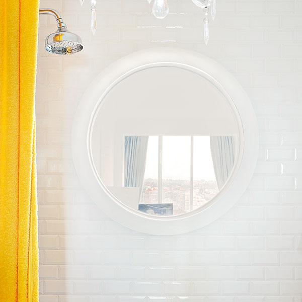 Originálne spojenie. Dizajnéri vymysleli aj spôsob, ako presvetliť aozvláštniť kúpeľňu na konci vstupnej chodby – lodné okno vsprchovacom kúte. Pri sprchovaní tak máte výhľad do obývačky.