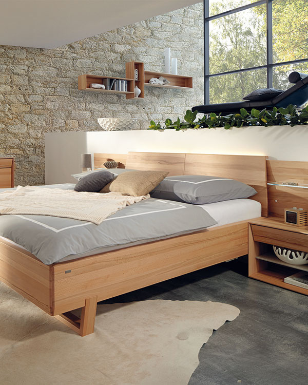 Masívna spálňová zostava Miava značky Hülsta vdrevenom dekóre štruktúrovaného buka. Zostavu jemne ozvláštňujú zvýraznené čielka na nočných stolíkoch akomodách. (Predáva Merito.)