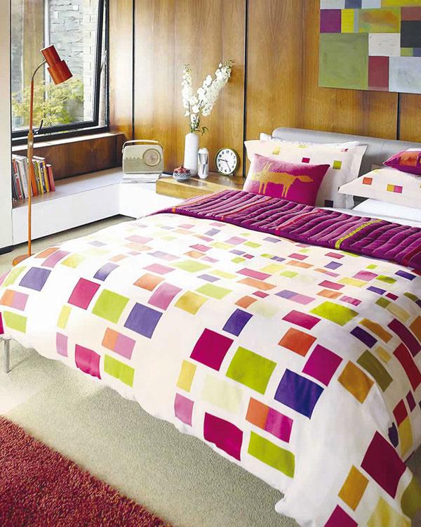 Textílie aobliečky sfarebnými geometrickými vzormi na bielom pozadí zretrokolekcie Scion Blocks skvelo dopĺňajú prikrývky srovnakými farbami. (Predáva Cymorka Interior Design.)