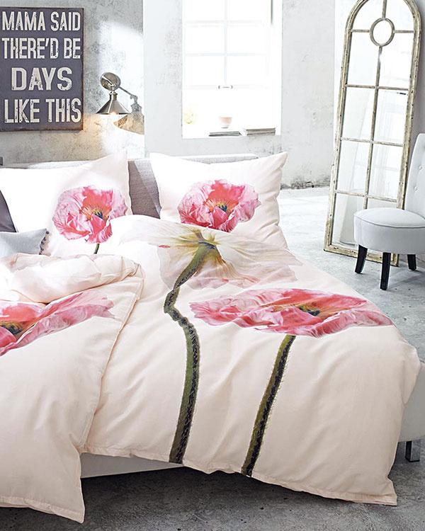 Štýlovo spriestorom zladená posteľná bielizeň sveľkými kvetmi, ktorých vôňu vtomto interiéri skoro môžeme cítiť. So šarmom zmenili tvrdú betónovú miestnosť na jemnú ženskú spálňu. (Predáva www.impressionen.de.)