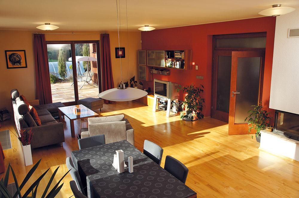 Príjemný charakter dodávajú obývacej izbe nielen slnečné lúče, ale aj zlatisté odtiene javorovej podlahy, dverí anábytku sčerešňovou dyhou.