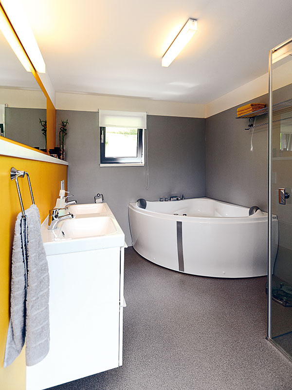 Kráľovská kúpeľňa. Hoci rozloha domu nie je nijako závratná, venovali architekti kúpeľni pomerne veľkorysý priestor – vošli sa sem dve umývadlá, veľká rohová vaňa aj priestranný sprchovací kút.