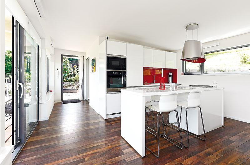 2 v1. Pretože sa na 80 m2 muselo šetriť miestom, jedáleň je vlastne pokračovaním pracovnej plochy kuchynského ostrova. (Pohľad zobývačky smerom kvchodovým dverám)