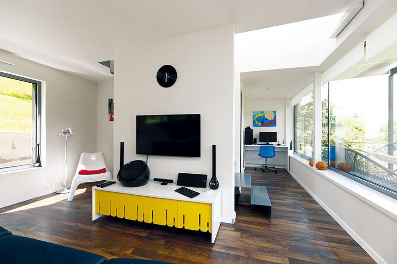 """Kúzlo svetla afarieb  Malý priestor pôsobí vzdušne, za čo vďačí hojnosti svetla, striedmemu zariadeniu aprevahe bielej farby. Farebné akcenty vnášajú do interiéru červené, žlté amodré doplnky, ktoré odkazujú na exteriérovú farebnosť """"včelích úľov""""."""