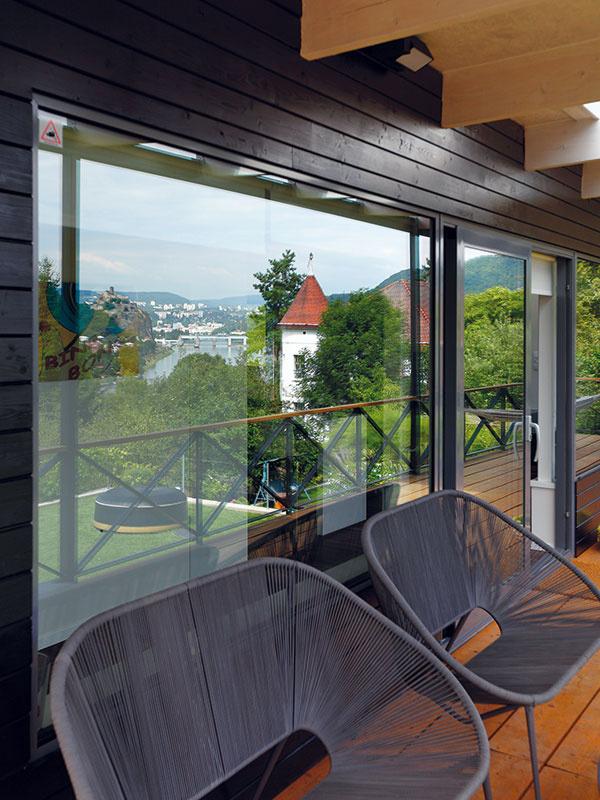 100 % výhľadu. Keď nie je práve počasie naužívanie si slniečka alebo vírivky na trávnatej terase, môžu majitelia aj ich návštevy relaxovať vpohodlných kreslách na krytej drevenej terase pred domom akochať sa výhľadom.