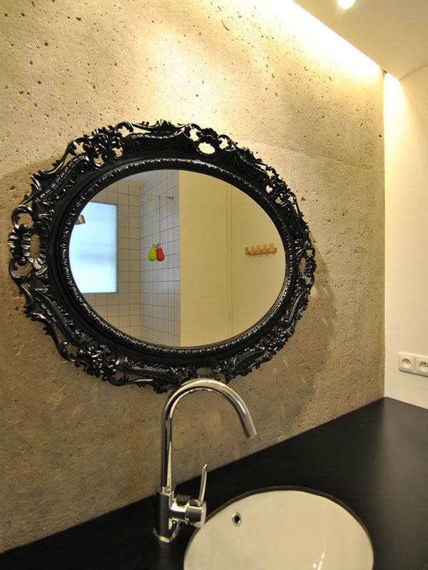 Pôvodná betónová stena sa po odhalení stala šperkom kúpeľne. Skvele sa na nej vyníma ozdobné zrkadlo v čiernom ráme. Efektné nasvietenie mu dodáva punc umeleckého diela.