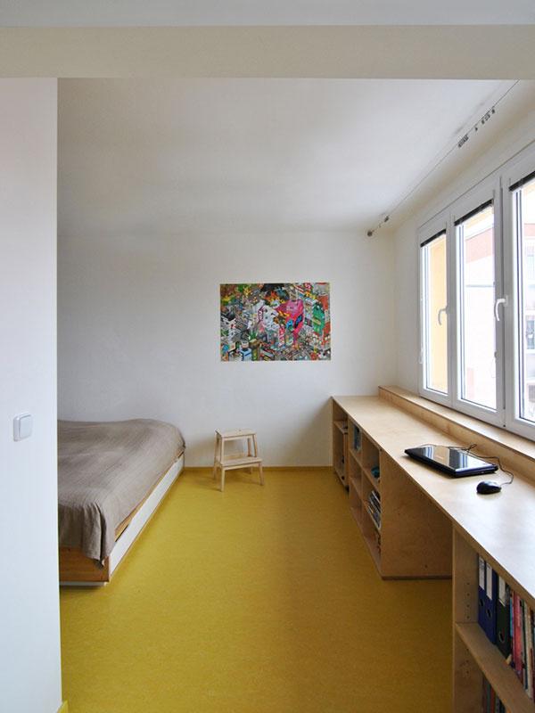Pod oknami v spálni stojí pracovný stôl s policami, vytvárajúcimi knižnicu. Pracovný priestor pri okne je praktický, pretože naň dopadá dostatok denného svetla.