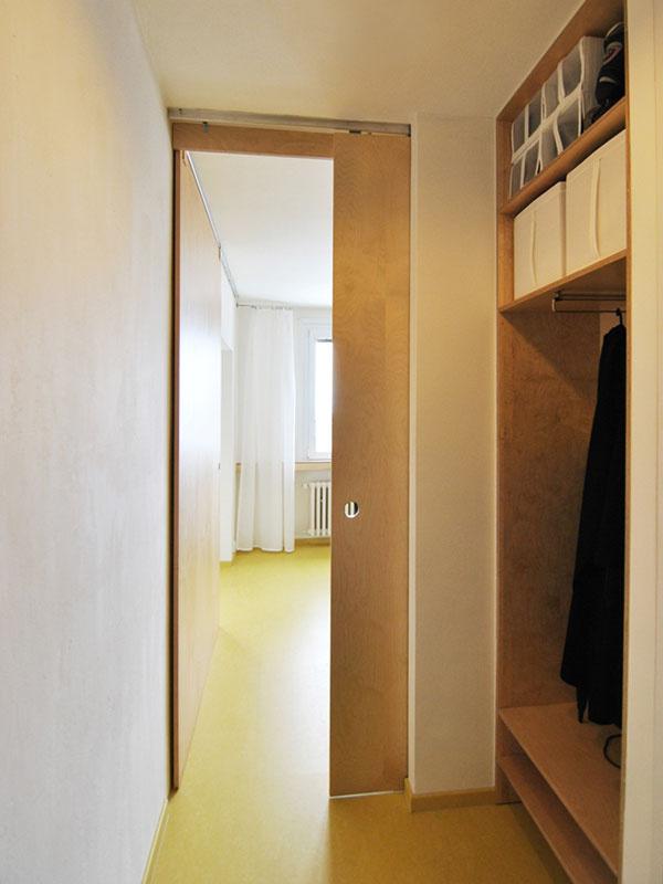 Malá predsieň s nikou na kabáty a príjemný priehľad do kuchyne smerom k oknu. Hladké posuvné dvere nemajú kľučku, ale len okrúhly otvor na prsty.