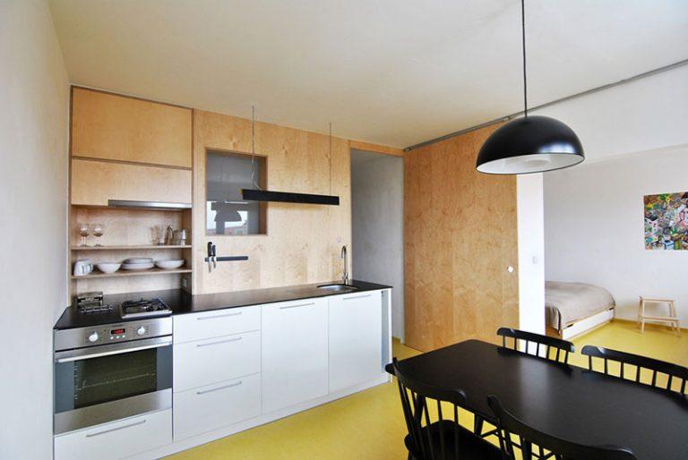 Hlavným priestorom je spojenie jedálne a spálne. Dominuje  kuchynská linka s čiernou doskou z Compactu, ktorý ladí s ostatnými čiernymi predmetmi v interiéri.