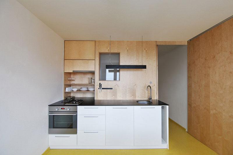 Do jednoduchej kuchyne so stenou z preglejky vedie presvetľovacie okienko, ktoré privádza denné svetlo do kúpeľne. Zaujímavý a praktický detail: nože a kovový riad je možné umiestniť na magnetickú lištu.