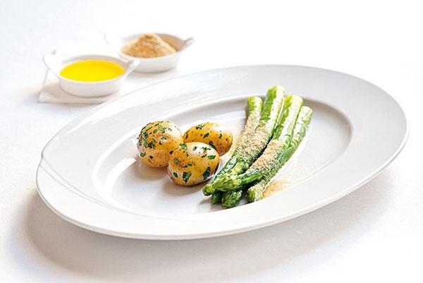 """Varená špargľa s maslom a strúhankou Obrázok č. 2  Potrebujete: 800 g zelenej špargle 125 g rozpusteného masla Štipka soli a čierneho korenia 1 kg nových zemiakov – umytých a uvarených v šupke Strúhanka  Postup:  Najprv olúpte špargľu a spodné časti odlomte – môžete ich použiť napríklad na prípravu špargľovej polievky. Do Multicookera nalejte 1,5 l vody, pridajte 1 lyžicu cukru, 1 dl citrónovej šťavy a trochu soli. Multicooker nastavte na funkciu BOIL, priveďte vodu do varu a na naparovacie sitko naukladajte špargľu. Môžete ju tiež variť zviazanú kuchynskou niťou v hrnci hlavičkami nahor tak, aby boli tesne nad tekutinou. Varte asi 3 až 5 minút. Špargľa by nemala byť pri zahryznutí príliš mäkká, ale pevná (""""al dente""""). Odkvapkanú špargľu uložte rovnobežne na predhriaty tanier, prelejte maslom, posypte opraženou strúhankou. Ako prílohu podávajte nové zemiaky varené v šupke."""