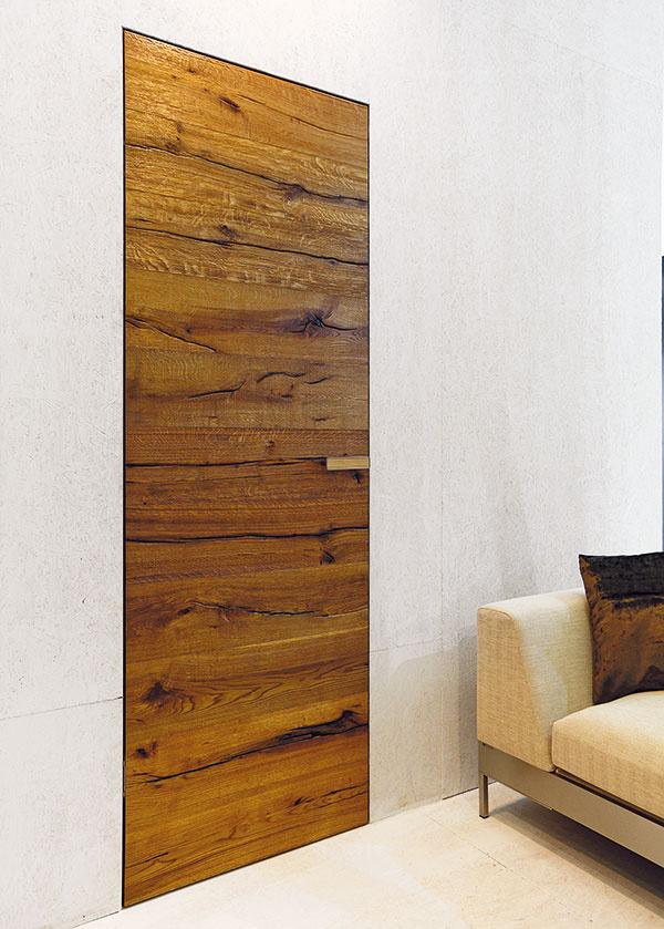 """Výrobca interiérových dverí zPrievidze Wens door nás celkom dostal spojením rustikálneho vzhľadu hrubo opracovaného dreva svýraznou štruktúrou aelegantného, čistého detailu osadenia dverí bez zárubne. Ikeď so silnými kontrastmi treba narábať opatrne, takéto dvere môžu byť naozaj pôsobivou """"čerešničkou"""" vjednoduchom, moderne zariadenom interiéri."""