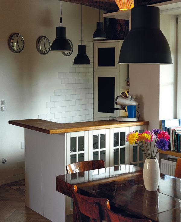 """Kuchyňa tvorí vdennej miestnosti priestorový """"záliv"""", ktorý tvaruje do väčšej hĺbky barový pult. Na ten priamo nadväzuje veľký jedálenský stôl."""