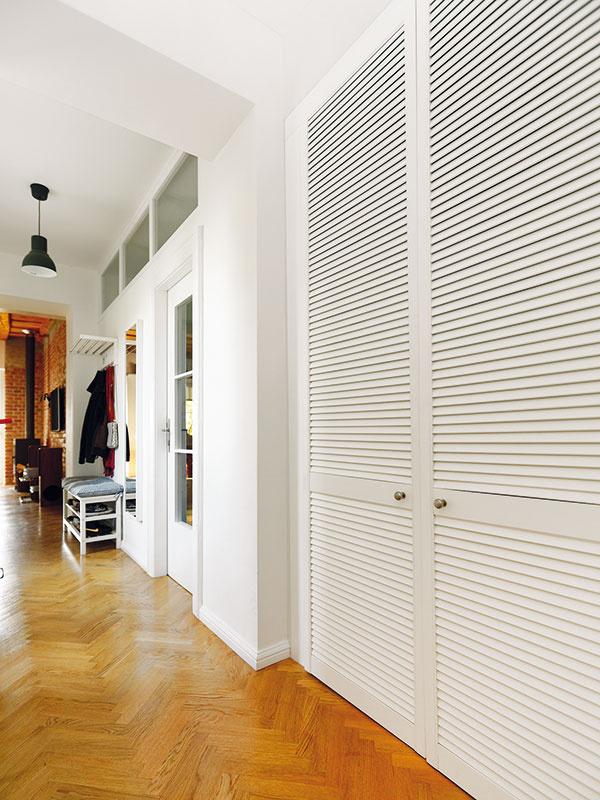 Praktický šatník. Nových priečok nebolo veľa, mali však logické umiestnenie avdispozícii dôležitý účinok – napríklad vo veľkej, neúčelne tvarovanej chodbe vznikol praktický šatník, skrytý za bielymi lamelovými dverami.