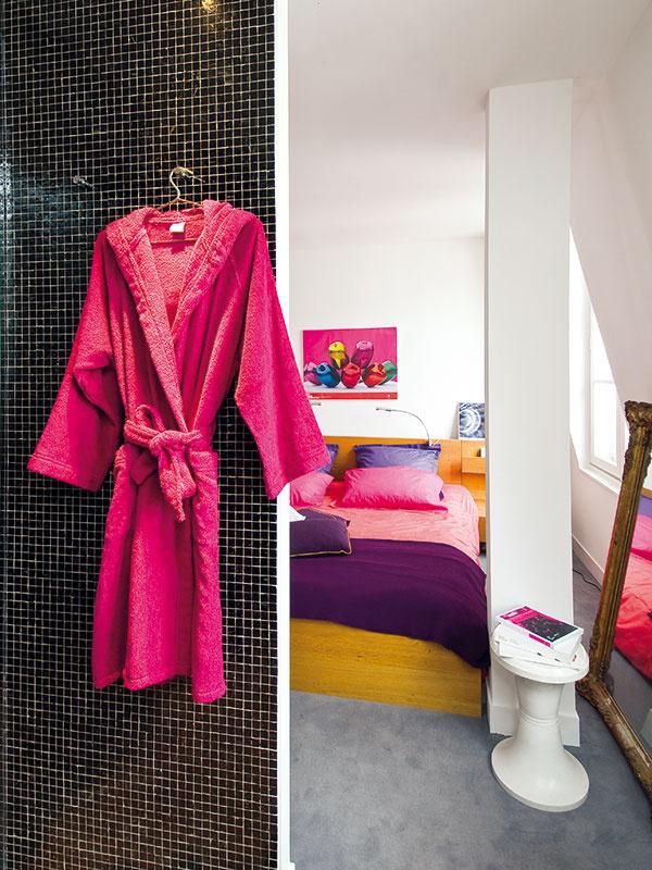 Spálňu a kúpeľňu oddeľuje len krátka priečka. Farebne neutrálny základ, ktorý vytvorili biele, sivé a čierne plochy podláh a stien, oživujú najmä jasné ružové textílie a doplnky.