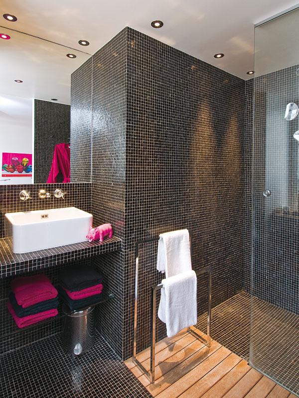 Kúpeľňa so stenami a podlahou pokrytými lesklou čiernou mozaikou pôsobí exoticky. Pocit tepla dodávajú drevo a farebné textílie.