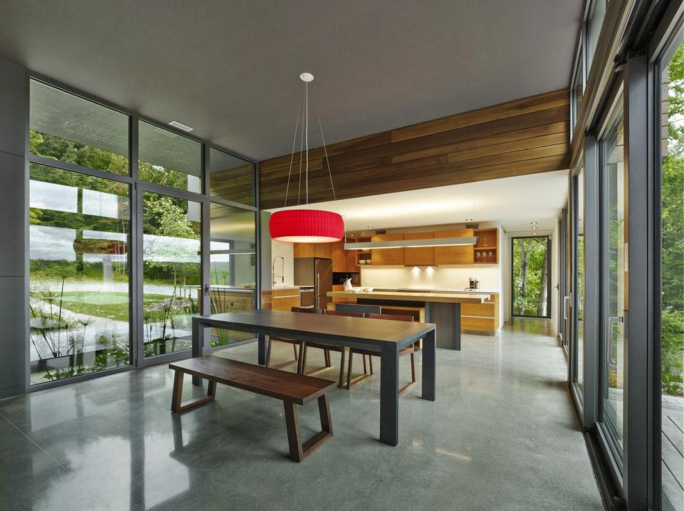 Prechodová zóna v centre stavby, kde sa nachádza srdce domu v podobe kuchyne a jedálne, je transparentným priestorom poskytujúcim úžasný výhľad na všetky strany.