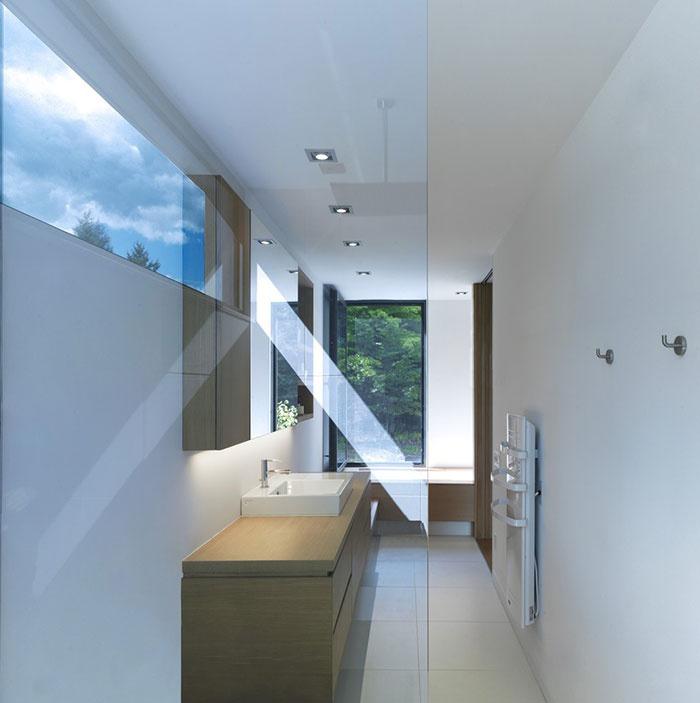 Práca s rôznymi formátmi a výškami okien v kombinácii so sklenenou priečkou a bielymi stenami učinila z kúpeľne vzdušný, ľahký priestor, kde nie je núdza o svetlo.