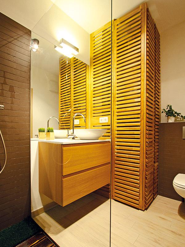 Piešťanské kúpele. Síce len ich miniatúra, ale predsa. Zmena dizajnového štýlu vporovnaní so zvyškom bytu nastala pre požiadavku na vytvorenie teplého interiéru vpriveľmi stiesnenej kúpeľni. Za dreveným latovaním je ukryté všetko, čo by pohľadu zavadzalo, aelegantné narábanie sdrevom je zásahom do čierneho.