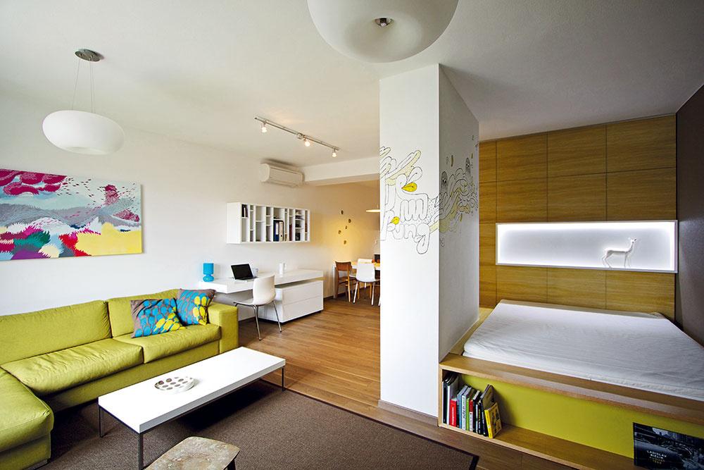 Prípecok, alebo ako ho architekti vtomto prípade nazvali, zápecok, šikovne oddelil spálňu od zvyšku bytu. Plytká nika, slúžiaca na odkladanie drobností, má zároveň pridanú hodnotu svetelného zdroja atvarovo korešponduje sknižnicou zasunutou pod nohami vprednej časti postele.