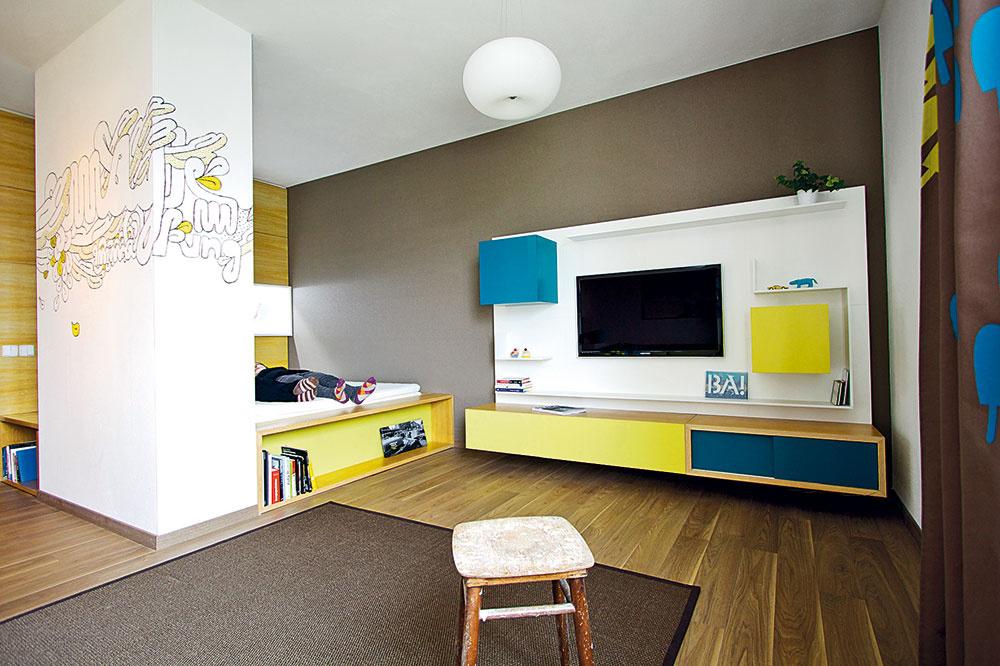 Rozihraná kompozícia obývačkovej steny narába stelevízorom ako sjedným zjej prvkov. Medzi kubusy skriniek apolice farebne zladené stextíliami príjemne zapadla.
