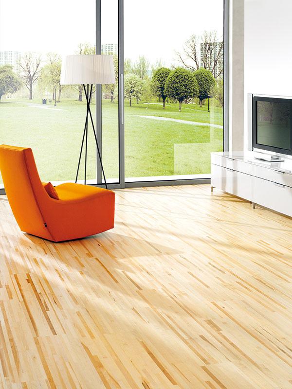 """Ak neholdujete aktuálne trendovému rustikálnemu vzhľadu drevenej podlahy ažiada sa vám niečo na pohľad výraznejšie, siahnite po """"melírovanom"""" dekore, ktorý vás rozhodne len tak nezačne nudiť. Pri takto výraznej podlahe však dobre zvážte výber nábytku. Minimalizmus ačisté línie sú vtakomto prípade nevyhnutnou voľbou. (kolekcia Hobo Furnierboden Longline, dekor javor, predáva Koratex)"""