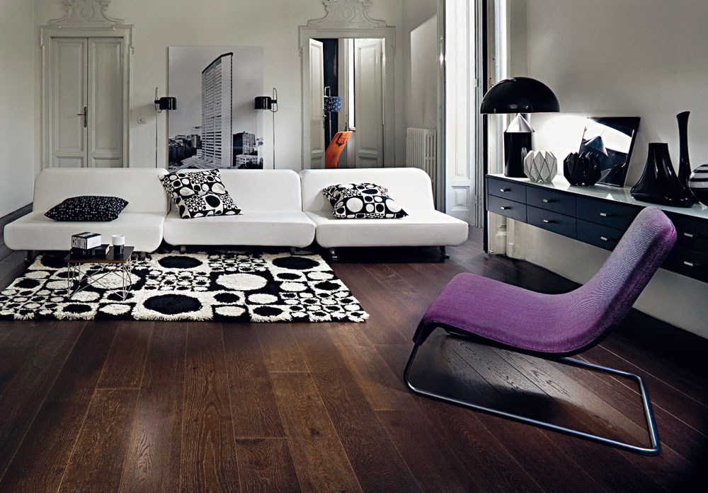 Veľmi zaujímavo pôsobia aj drevené podlahy snerovnou povrchovou úpravou. Takto spracovaný tradičný materiál má svoje nezastupiteľné miesto aj vmoderne ladených interiéroch. Tmavý teplý odtieň podlahy dodáva obývacej izbe ladenej do studených odtieňov bielej, čiernej afialovej útulnosť. (kolekcia Spirit, dekor Dub Forest, predáva KPP)