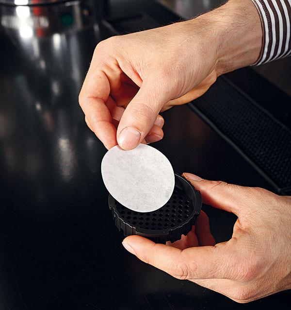 Do plastového sitka vložte papierový filter anavlhčite ho.