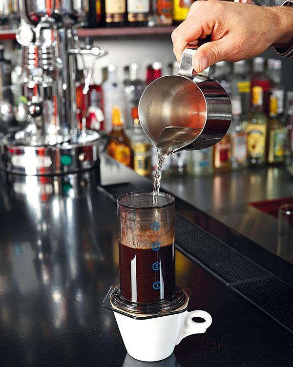 """Kávu pokvapkajte, aby napučala a""""rozdýchala sa"""". Chvíľu počkajte azalejte ju vodou (voda by mala mať asi 80 °C anemala by siahať nad značku 4)."""