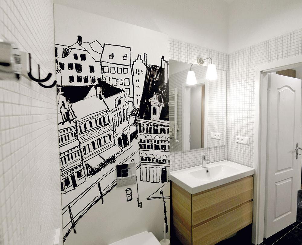 Pôvodné vs. moderné. Spolu sdrevenými podlahami je originálom aj pôvodná profilovaná zárubňa. Grafika ladiaca skuchynskou zástenou vytvorila zo zabudovaného Geberitu umelecké dielo. Autorkou je umelkyňa Alica Gurínová.