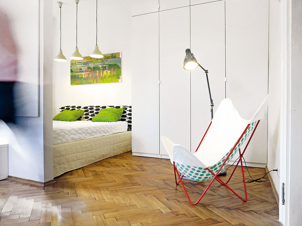 Skrine až po strop, nenápadne potlačené farebnosťou, sú hlavným úložným priestorom bytu. Vstrede vynechaná medzera slúži ako nika na zasunutie postele.