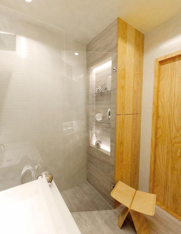 Vysoká skriňa, ktorá ukrýva slim práčku, je delená na dve časti. Dolná slúži len práčke adostatočnému priestoru nad ňou vprípade plnenia zvrchu. Horná, vybavená policami, poskytuje veľký doplnkový priestor až po strop. Vrámci deliacej priečky zo strany sprchovacieho kúta získame navyše niku na odkladanie kozmetiky, ktorá môže byť podsvietená LED pásmi.