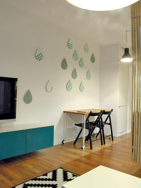 Kvapky na stene sú výsledkom spolupráce MIMOarchitektov s Michaelou Bednárovou, ktorá vytvorila dezén poťahovej látky. V kuchyni táto priestorová inštalácia nájde uplatnenie aj ako vešiaky.