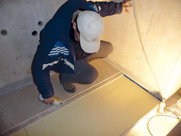 Po obvode miestnosti umiestnili izolačný pás, ktorý bráni prenosu krokového hluku medzi podlahou astenami aumožňuje dilatovanie podlahy. Potom položili dvojvrstvové podlahové dielce, na ktorých poldrážkové spoje naniesli vdvoch pruhoch podlahové lepidlo.