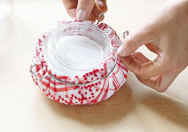 Sklenenú časť vrchnáka vložte do pripravenej utierky astiahnite ju nitkou. Nasaďte ju naspäť na vrchnák aten zasa na dózu.