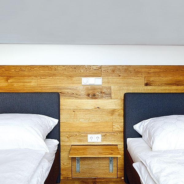 Postele vhosťovských spálňach sa dajú posúvať do dvoch polôh – buď sú spojené, alebo oddelené. Túto flexibilitu umožňujú originálne nočné stolíky, ktoré sa dajú sklopiť do roviny sobkladom alebo vyklopiť zo steny tam, kde ich potrebujete.