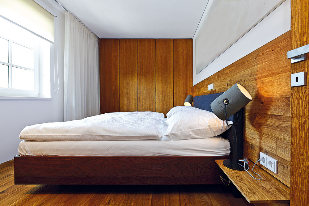 Vhosťovskej spálni dominuje drevo vo viacerých odtieňoch. Podlahové dosky využil architekt aj na stene za posteľou, kde chránia exponované miesta.
