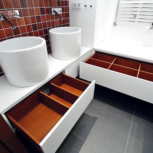 Vkaždej zkúpeľní sú vnábytku vyrobenom na mieru navrhnuté premyslené odkladacie priestory. Biele striekané skrinky tvoria kontrast ktmavej podlahe adrevenej tíkovej mozaike.