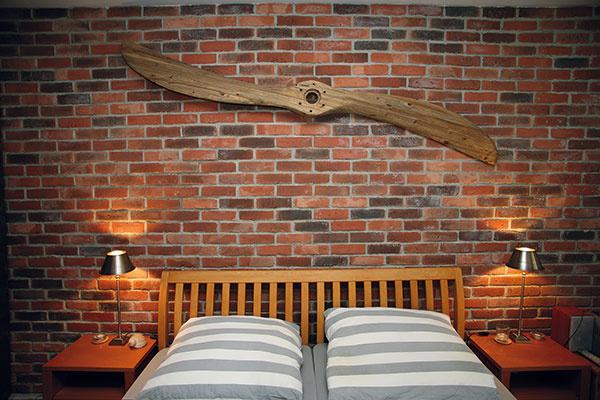 """Spálňa koloniálneho letca – dostala meno podľa drevenej vrtule zlietadla za posteľou. """"Otec bol letec, asi preto mám klietaniu akvrtuliam odmalička zvláštny vzťah."""""""