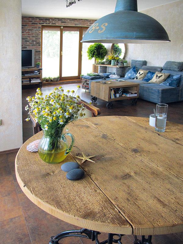 """Doska jedálenského stola je zo 100 rokov starého lešenia: """"Stolár znej musel osekávať betón,"""" spomína Peter. """"Má rovnakú farbu avýraznú štruktúru ako pieskované drevo na iných kusoch nábytku. Akoby ich vyplavilo more – tvrdšie časti dreva sú vystúpenejšie než mäkké,"""" popisuje snadšením."""