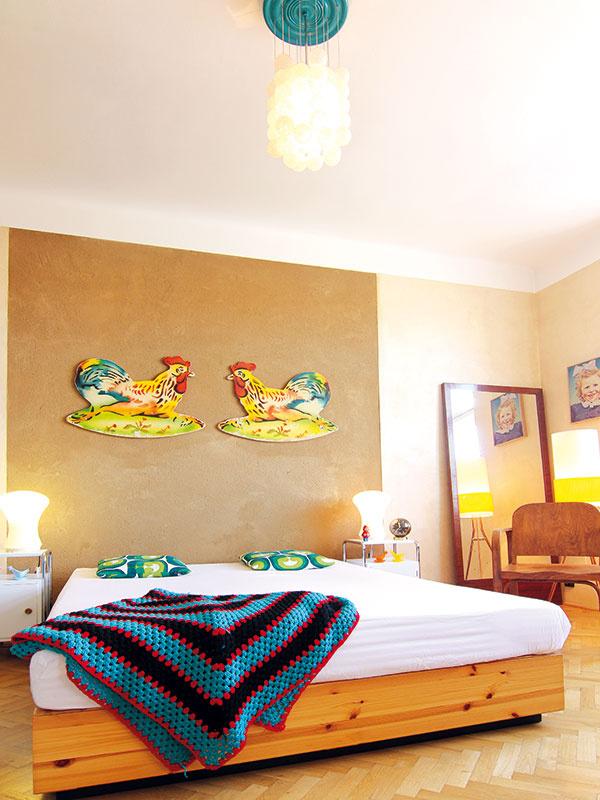 """Novú posteľ Ikea s""""čelom"""" tvoreným hlinenou omietkou dopĺňajú dobové nočné stolíky adrevené zrkadlo. Spálňa ako pozostatok pôvodnej obývacej izby je spolu skuchyňou avstupnou halou priestorom soriginálnymi dubovými parketami, ošetrenými záťažovým lakom, takže časté presúvanie nábytku im neublíži."""