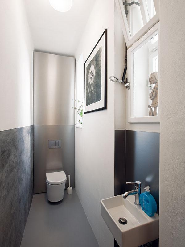 """""""Retro-industriál."""" Tak by sa dal charakterizovať štýl bytu, pričom hlavným nositeľom pojmu """"industriál"""" sa stalo WC. Metalické materiály majú funkciu odolných prvkov do vlhkého prostredia. Vzhľadom na plochu, ktorú WC získalo vďaka rozšíreniu opôvodnú komoru priliehajúcu ku kuchyni, sa sem manželom podarilo umiestniť aj malé umývadlo."""