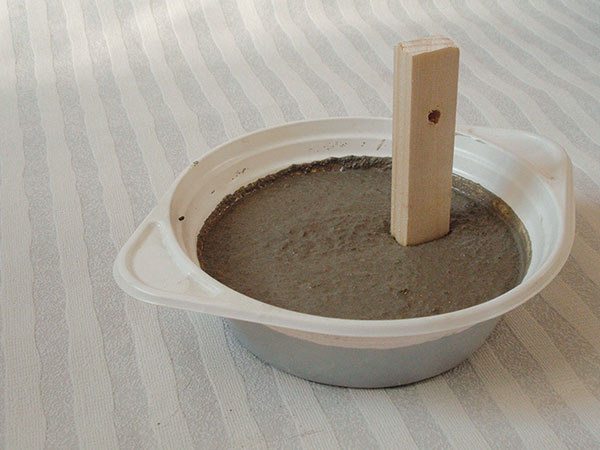 2 Výroba podstavca. Zarobte si betón svodou, vymiešajte ho, aby mal správnu konzistenciu, analejte do plastovej misky. Prevŕtaný kolík podstavca napevno vtlačte do misky sbetónom. Uistite sa, či je kolík rovno, anechajte betón zrieť. Po 6 hodinách môžete pokračovať vpráci, ideálne ale je nechať betón odstáť 24 hodín.