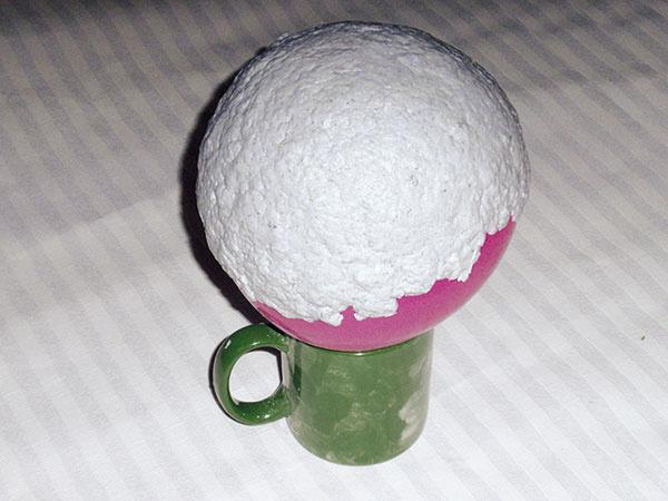 Výroba tienidla. Takto pripravenú hmotu naneste na nafúknutý balón. Mala by priľnúť kbalónu. Ak odpadáva, je vnej veľa vody alebo málo škrobu. Veľkosť balóna udáva veľkosť tienidla (minimálny priemer je 14 cm). Balón poriadne uviažte, aby počas schnutia hmoty nevyfučal. Nechajte schnúť minimálne 24 hodín. Keď hmota poriadne uschne, stačí balón opatrne vyfučať.