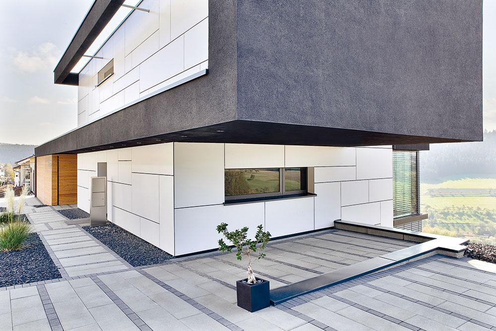 Presah horného poschodia vytvoril kryté parkovacie miesto. Zabudované LED diódy nie sú len estetickým prvkom, ale majú aj praktickú funkciu – osvetľujú prístupovú cestu.