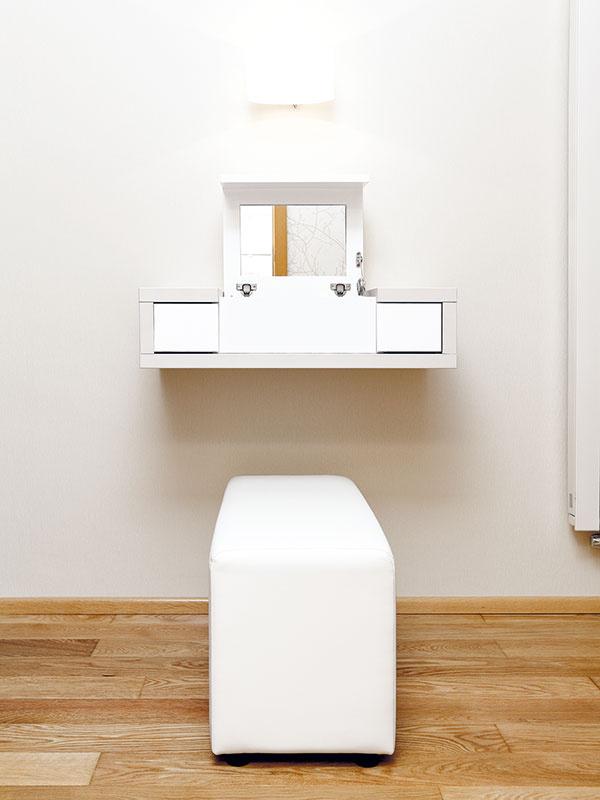 Otvárací toaletný stolík je vyrobený na mieru. Aj vspálni je, podobne ako vobývačke akuchyni, použitá decentná kombinácia niekoľkých odtieňov bielej azemitých tónov, tu je však, na rozdiel od kuchyne, povrch nábytku matný.