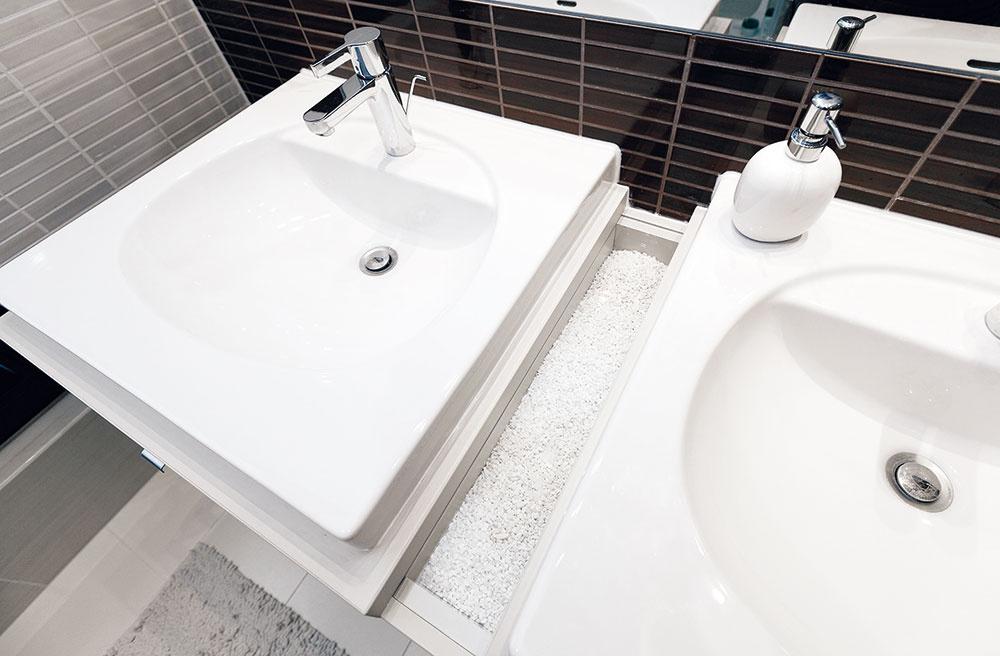 Skrinku pod umývadlá so zaujímavým detailom kamienkovej dekorácie aotvorom na uteráky potom vyrobili na mieru pôvodnej kúpeľni, azároveň vduchu nového zariadenia bytu.