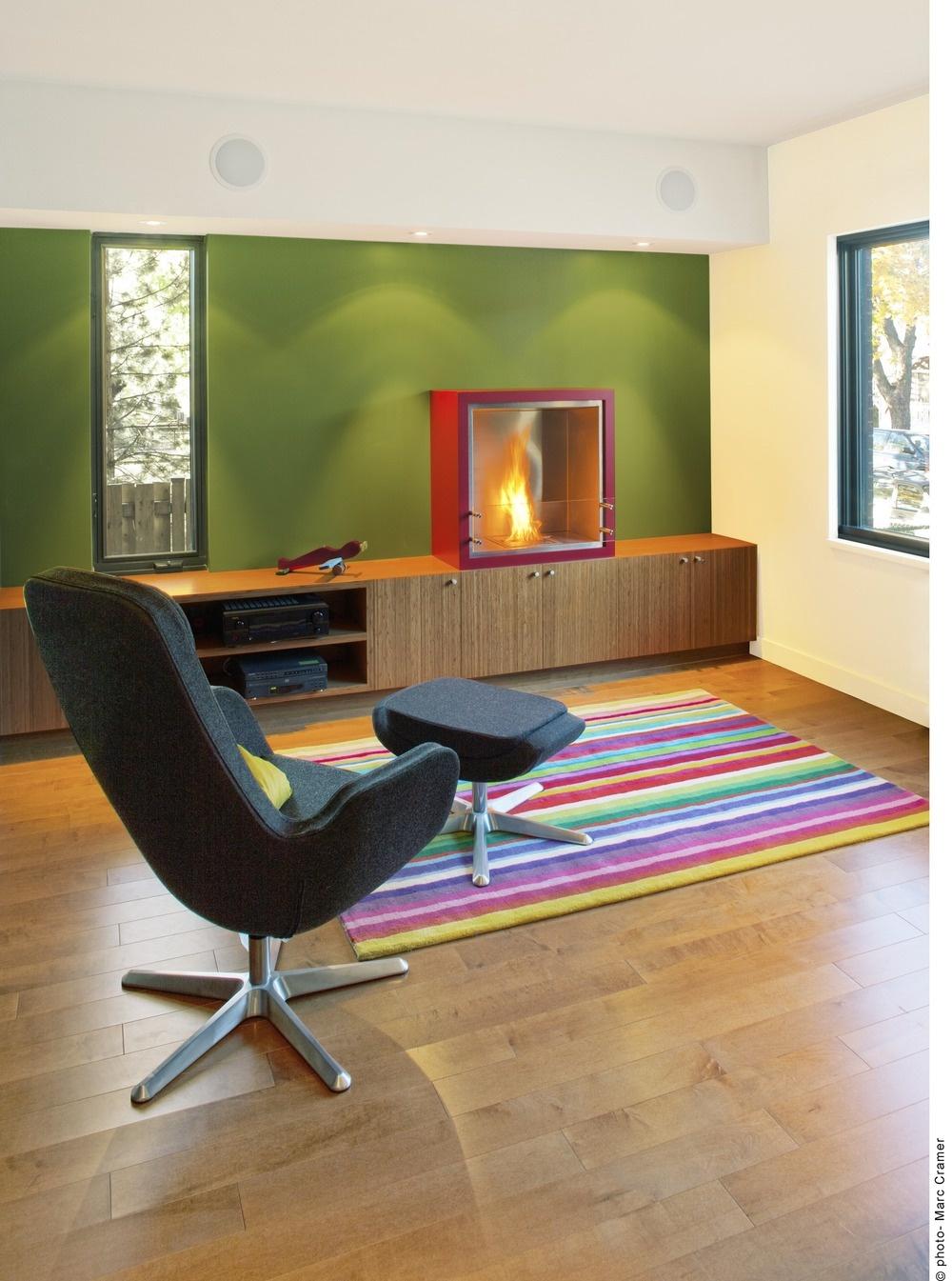 Pruhovaný koberec je jedným z mála farebných výstrelkov v tomto inak veľmi striedmom interiéri. Liehový kozub dotvára atmosféru pri posedení počas dlhých zimných večerov.