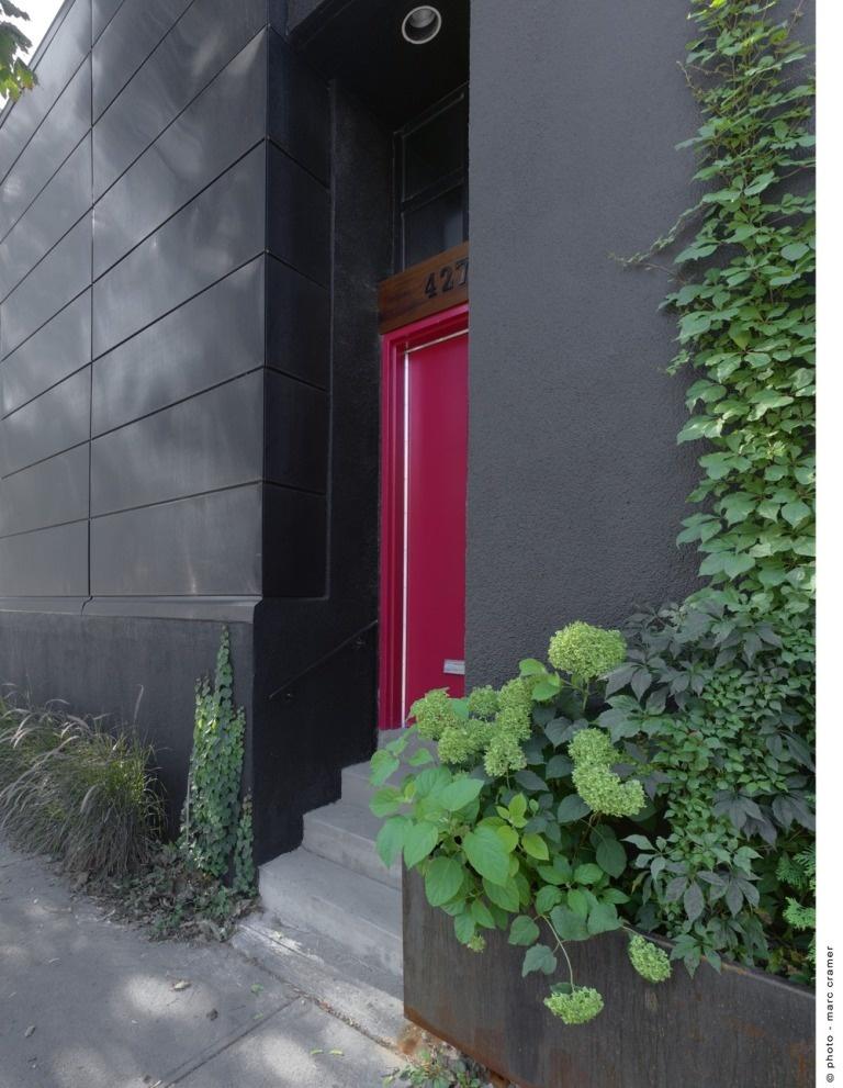 """Vchod do domu, na ktorého streche vytvorila šikovná architektka pôsobivý """"byt"""" na čerstvom vzduchu. Čierna plocha fasády sa v strešnom priestore zámerne opakuje."""