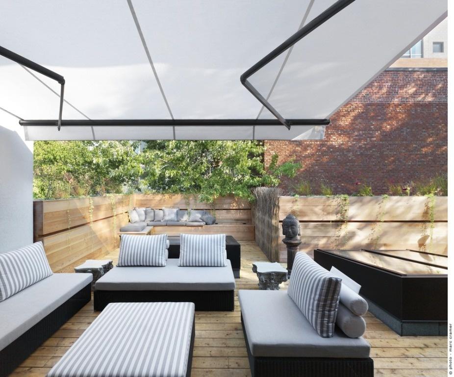 Obývačku obklopuje nízky múr, ktorého štruktúru tvoria vegetačné nádoby a vytvárajú tak príjemnú zelenú hradbu. Vďaka vegetácii vznikla prirodzená zástena ako úkryt pred okolím celej strešnej terasy.